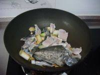 酸菜鱼,锅里放油,炒香葱姜蒜。下入鱼头鱼尾鱼骨块鱼皮炒变色。