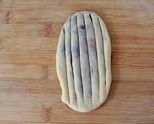 红豆沙面包卷,将包好红豆沙的面团按扁、擀成长舌状,用刀划出纵向纹路。