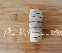 红豆沙面包卷,翻面。从没有纹路的一端卷起,接口处捏紧,整理好形状。