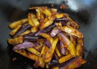油淋茄子,下茄子条,翻炒,加酱油和白糖调味。这一步也不要炒太久,味道炒匀后就行。茄子过油后已经熟了,炒太久就烂了,没有看相。