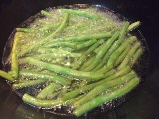 干煸豆角,如图锅中加入小半锅油,将沥干水分的四季豆放入锅中炸