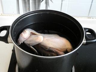 私房白切鸡,将三黄鸡放入加入温水的锅中。