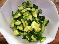 刀拍黄瓜,将黄瓜块用盐腌制5分钟,将腌制出来的黄瓜汁倒掉