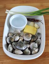 酒蒸蛤蜊,清水加入少许盐,滴一滴食用油,放入蛤蜊静养2小时,让其充分吐出脏东西,洗净沥干。葱姜洗净。