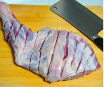 迷迭香孜然烤羊腿,把羊腿洗净用清水泡10分钟,然后沥干水,两面都用刀划成深痕。
