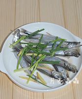 香煎椒盐多春鱼,把处理好的多春鱼放点料酒、姜片和葱段,腌制一会儿去腥。