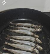 香煎椒盐多春鱼,平底锅烧热,放入一茶匙色拉油,把腌制好的多春鱼用厨房纸巾拭干表面水份,排入锅中。