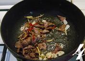 火爆猪肝,放入泡红辣椒、姜丝、蒜片一起炒出香味。