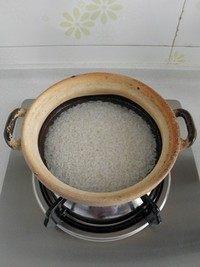 腊味煲仔饭,在砂锅底部抹一层油,再将泡好的大米沥干水放入砂锅,倒入清水(水要超过大米约1cm)。盖上锅盖中小火煮开后再焖煮10分钟左右。