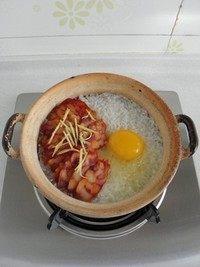 腊味煲仔饭,将腊肠摆在米饭上,在把姜丝放在腊肠上,将鸡蛋打在一边,再沿着锅边倒适量的油。