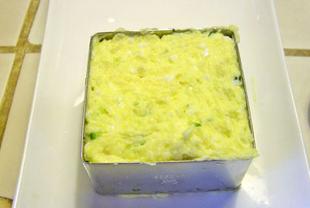 土豆沙拉,在盘子中间放一个慕斯圈,这么做是为了给土豆沙拉造型,没有慕斯圈也没关系,将土豆沙拉盛入碗中倒扣成球状也行。将拌匀的土豆泥盛入慕斯圈中,抹平,去掉慕斯圈。