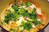 酸汤肥牛,把煮熟的菜和肥牛放入番茄汤中,加盐调味,撒葱花和香菜末,关火