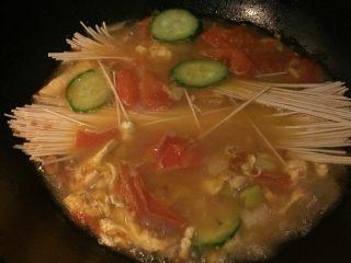 西红柿鸡汤面,如图加入黄瓜片和面条(手擀面,挂面均可)盖上锅盖大火烧开,转小火煮10_15分钟,根据苗条的粗细决定时间。