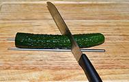 蓑衣黄瓜,黄瓜洗净去掉尾部,用2根筷子夹住黄瓜,45度方向斜着下刀将黄瓜切片,切到筷子处为止。