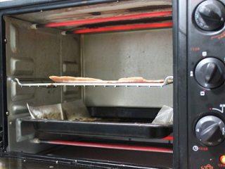 自制猪肉脯,烤箱200度预热好后,冻好的肉片取出,撕去全部保鲜膜,放在烤架上,这一步取出来撕掉膜马上烤,时间长了肉解冻软了就不好操作了,中层,下面用烤盘垫油纸或锡纸接油