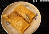 素鸭(家庭版),锅中放油,小火将蒸好的豆油皮卷煎到两面焦黄。素鸭的样子已经可以看出了。