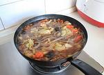 大锅菜,加入适量的白开水和泡好的红薯粉条,盖上锅盖大火烧开后转小火炖煮至粉条变软无硬心。