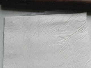 北京奶酪卷,装入保鲜袋中,用擀面杖擀平