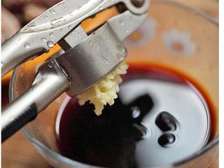 黑木耳拌鸭胗,将适量生抽倒入碗中,用压蒜泥器压出蒜泥放入碗中