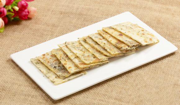 香椿脆饼,锅中倒入油,将擀好的面饼放入锅中,煎至一面微黄后,翻边煎另一面,煎至酥脆时盛出,置于砧板上,切块,就可以食用了