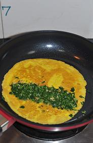 马兰核桃鸡蛋卷,把蛋饼翻个面,放上拌匀的马兰头拌核桃,用手稍稍整形并捏紧。