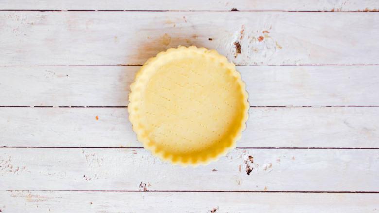 柠檬塔,使用前将塔皮从冰箱取出,在保鲜袋中擀开后铺在模具中,并用叉子在其底部戳孔,防止烘烤时过于膨胀