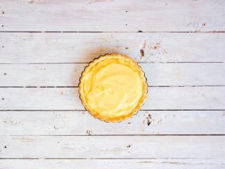 柠檬塔,将烤制半熟的塔皮取出,铺入柠檬酱,尽量抹平整