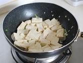 家常烧豆腐,放沥水后的豆腐,小心的晃动锅子,让豆腐均匀的沾到花生油方便定型。
