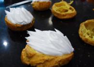 天鹅泡芙,烤好的空心泡芙均匀切开,分割成两层,下层挤上羽毛状的奶油,上层剪出两个翅膀的形状。最后将烤好的脖子插入奶油,翅膀呈飞翔状态插在奶油两边,装饰就完成啦。