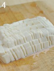 荠菜豆腐羹,<a style='color:red;display:inline-block;' href='/shicai/ 5179'>嫩豆腐</a>在盒子底部对角各剪一个小口子,倒扣底部朝天,用刀背轻轻拍几下。撕去表面薄膜,倒扣在案板上,切成小块。