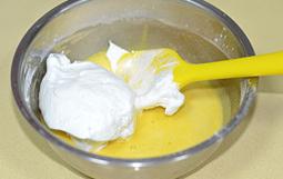 草莓蛋糕卷,将1/3打发好的蛋白加入到蛋黄糊中,用切拌和翻拌的方式拌匀。