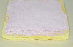 草莓蛋糕卷,烤好的蛋糕出炉凉晾后底部垫一张油纸,翻面后将草莓奶油涂上,头端划二刀不划透。