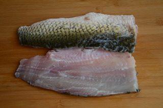 酸菜鱼,剁下鱼头和鱼尾,剪去鱼鳍,从连着鱼头的那端下刀,紧贴着鱼骨,斜刀将鱼肉剔下来