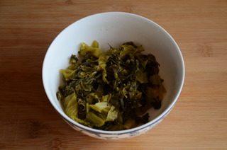 酸菜鱼,酸菜在开水中汆烫下,捞出冲洗后沥干水分,切成细丝