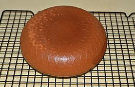 海绵蛋糕,烤好后电饭煲会发出蜂鸣提示,将电饭煲内胆从10CM左右的高度向桌面震一下,防止蛋糕回缩,然后将蛋糕倒扣在晾架上晾凉。