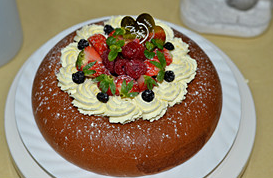 海绵蛋糕,打好的奶油装入裱花袋,在蛋糕表面挤上一圈,再用水果装饰,最好筛上少许糖粉即可.