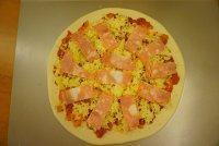 黑橄榄培根虾仁披萨,铺入培根片,铺上圆椒、玉米粒、黑橄榄