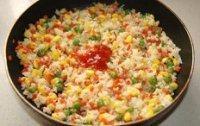 蛋包饭,待米饭彻底炒散,颗粒分明时加入盐,胡椒粉调味,再调入一大勺番茄酱炒匀
