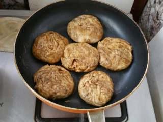 麻酱芝麻烧饼,将面卷分成均匀的小分,摁成烧饼胚,放在平底锅,放在火上稍微加热。