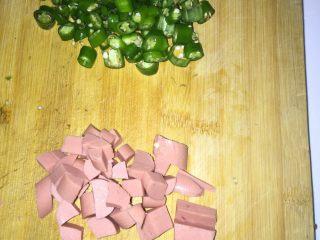 黄金炒饭,将火腿肠和青椒切成丁,和生姜蒜一起倒入烧好的油锅