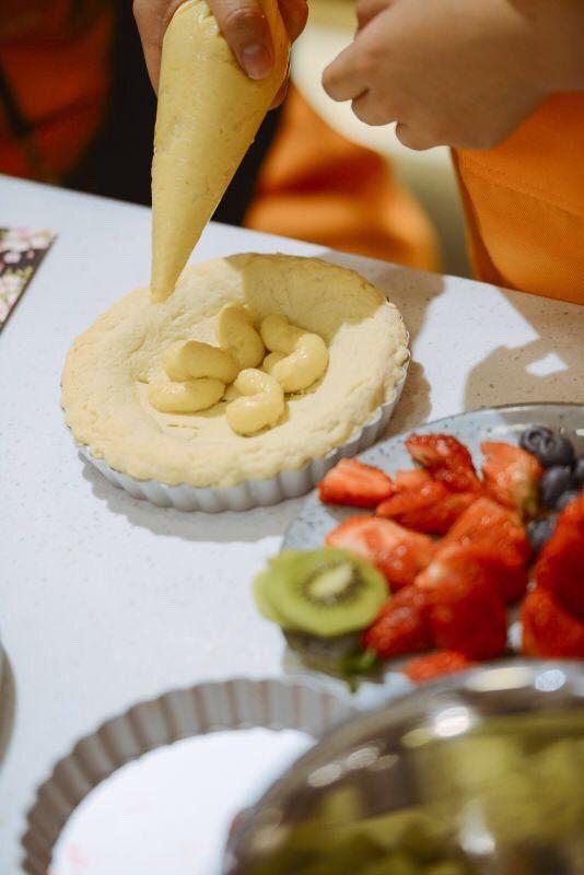 #春日烘焙教室#草莓塔/水果塔,柠檬奶油馅装入裱花袋,挤入准备好的塔皮。用刮刀抹平。