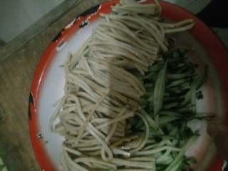 豆腐丝拌黄瓜,装在盛有黄瓜丝的盘子里