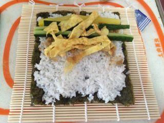 寿司,在铺好的米饭上依次放上肉松,黄瓜条,鸡蛋皮,萝卜条等你喜欢吃的东西。