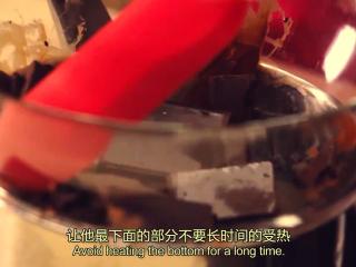 橙香米蛋糕,平底锅,倒少许水,用小火,把水烧热,接着黑巧克力放碗里,放在热水上隔热融化,融化的温度不宜超过55度