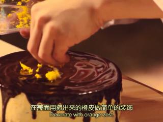 橙香米蛋糕,蛋糕从冰箱取出脱模,散热,淋上巧克力甘纳许,再用橙皮做简单装饰