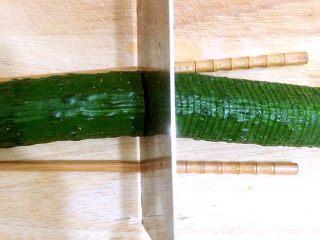 蓑衣黄瓜,刀子下落与黄瓜的角度呈90度,切片,底部不切断,放筷子就是防止切断,切完整根黄瓜