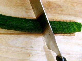蓑衣黄瓜,黄瓜翻转180度,没切的部分朝上,此次切片,刀子与黄瓜的角度变为45度斜切,依次切完