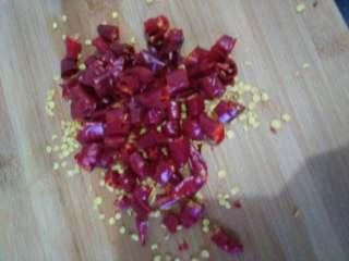 蓑衣黄瓜,将辣椒切段,锅内倒入油,凉油放入辣椒小火炸制辣椒有点变色后放入一把芝麻继续炸到辣椒有点焦黄色出锅