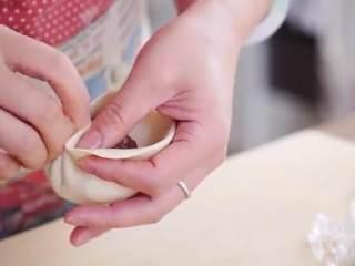 鲜肉包子,舀一勺肉馅放中间,捏起一个角形成褶,把面捏在褶上