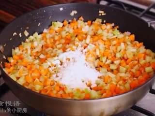 牧羊人派,再倒油,放入红葱头,翻炒至透明,加入迷迭香、西芹和胡萝卜丁翻炒,再加入面粉